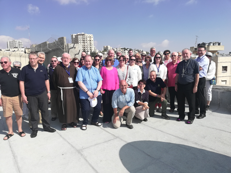 The Director and Engineer with members on the roof of the Bethany Creche East Jerusalem with the Seperation Wall in the background
